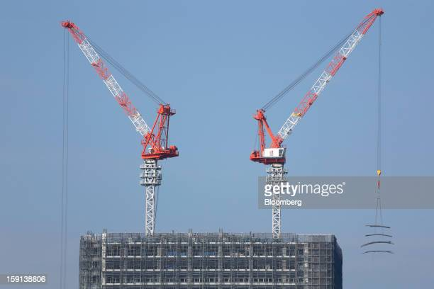 Cranes operate on a construction site in Tokyo Japan on Tuesday Jan 8 2013 Prime Minister Shinzo Abe aims to compile Japan's economic stimulus...