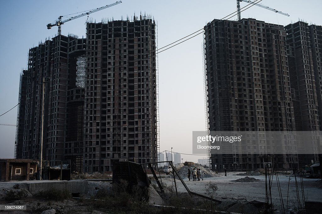Cranes sit atop apartment blocks under construction in Noida, Uttar Pradesh, India, on Wednesday, Jan. 9, 2013. India's Finance Ministry predicts GDP growth of as little as 5.7 percent in the year to March 31, the least in a decade. Photographer: Sanjit Das/Bloomberg via Getty Images