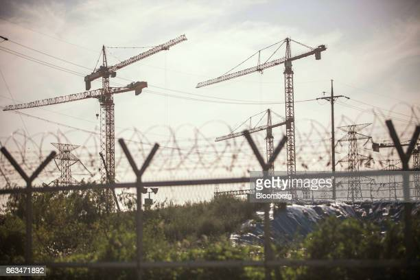 Cranes stand behind a fence at the temporarily suspended construction site of the ShinKori No 5 and 6 nuclear power reactors owned by Korea Hydro...
