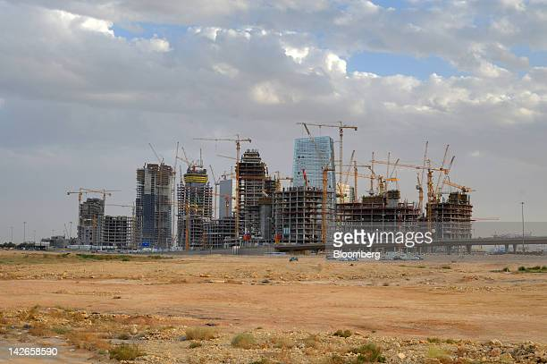 Cranes stand beside new high rise buildings under construction in the King Abdullah financial district of Riyadh Saudi Arabia on Monday April 9 2012...