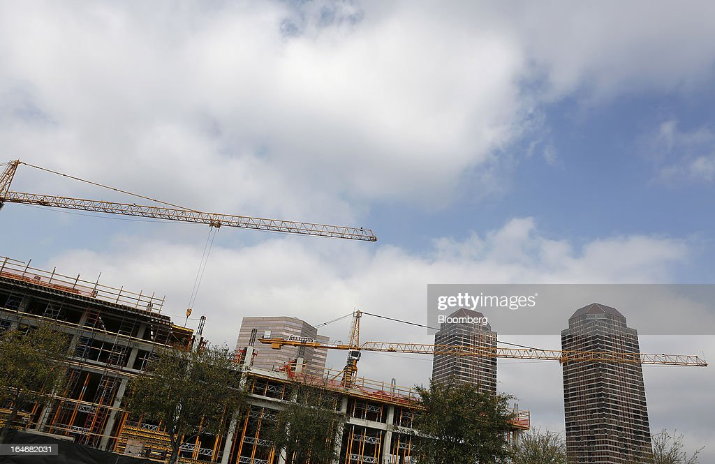 Cranes stand on the top of a building under construction in Houston, Texas, U.S., on Monday, March 18, 2013. Office sales in Houston, the fourth-largest U.S. city, jumped 32 percent last year to $3.89 billion, the highest total in five years and outpacing the 21 percent gain for the entire U.S., according to the research firm Real Capital Analytics. Photographer: Aaron M. Sprecher/Bloomberg via Getty Images