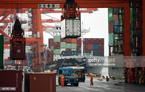 Cranes unload containers from a freighter at a container wharf in Tokyo port on October 22 2014 Japan's trade deficit expanded 16 percent yearonyear...