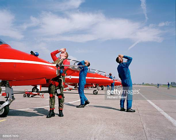 Craning their necks skyward both a pilot and support ground engineers of elite 'Red Arrows' Britain's prestigious Royal Air Force aerobatic team gaze...