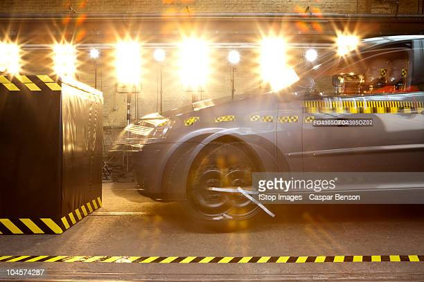 A crash test car with a crash test dummy driving into a barrier