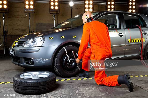 A crash test dummy changing a tire