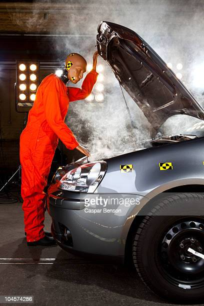 A crash test dummy checking under the hood of a smoking car
