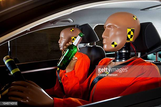 A crash test dummy drinking a beer while driving with a crash test dummy passenger