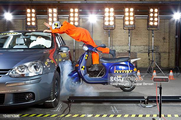A crash test dummy on a scooter crashing into a car