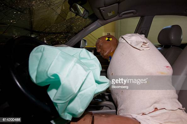 A crash test dummy sits behind a deployed airbag inside a damaged Hyundai Motor Co NF Sonata automobile following a crash test at the Korea...