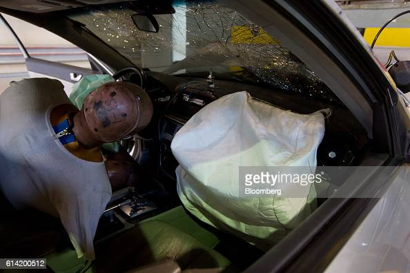 A crash test dummy sits behind deployed airbags inside a damaged Hyundai Motor Co NF Sonata automobile following a crash test at the Korea Automobile...