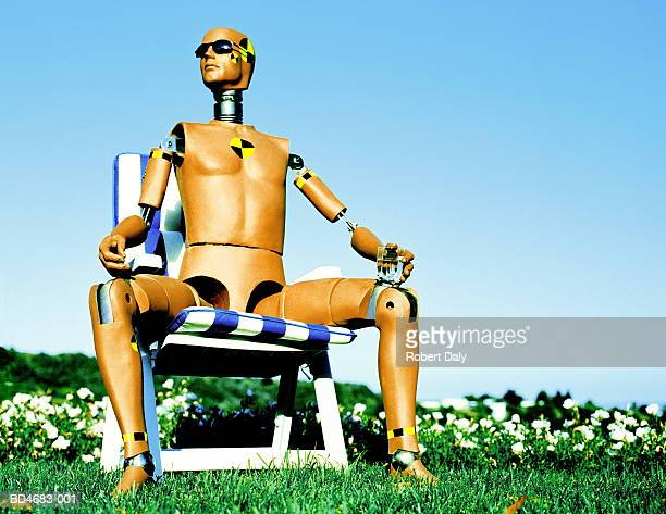 Crash test dummy sitting on garden chair, holding drink