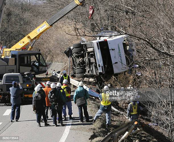 A crashed bus is lifted with a crane from a roadside slope in Karuizawa in Nagano prefecture central Japan on January 15 after it ran off a mountain...