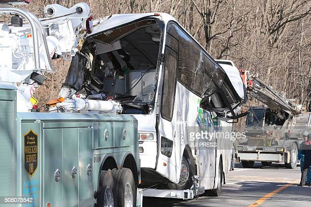 A crashed bus is pulled by a tow truck in Karuizawa in Nagano prefecture central Japan on January 15 after it ran off a mountain road Fourteen people...