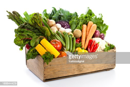 Crate filled with assortment of  organic vegetables on white backdrop