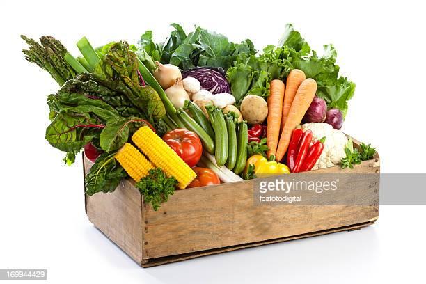 Caisse avec assortiment de légumes biologiques sur fond blanc