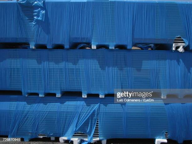Crates Covered With Torn Blue Plastic