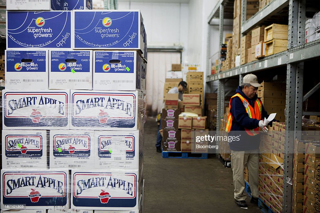 Crates of apples sit stacked as employees stock the Specialty Produce warehouse in San Diego, California, U.S., on Friday, Nov. 1, 2013. The U.S. Bureau of Economic Analysis is scheduled to release gross domestic product (GDP) figures on Nov. 7. Photographer: Sam Hodgson/Bloomberg via Getty Images