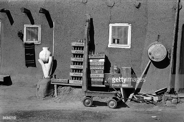Crates of CocaCola are piled up by the side of a house in Santa Fe New Mexico together with a small trolley and a wooden 'sculpture' a tin bath hangs...
