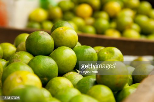 crates of green limes at a farmers market : Stock Photo