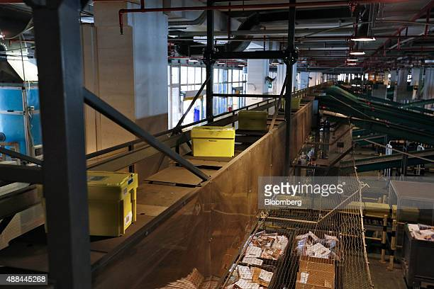 Crates travel on conveyor belts inside a Poste Italiane SpA postal sorting office in Fiumicino near Rome Italy on Tuesday Sept 15 2015 Italy is...