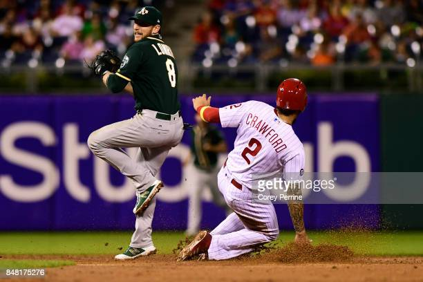 P Crawford of the Philadelphia Phillies is safe at second base as Jed Lowrie of the Oakland Athletics can't lay down the age in time during the sixth...
