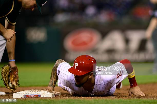 P Crawford of the Philadelphia Phillies makes it back safely to first base as Matt Olson of the Oakland Athletics can't make the tag in time during...