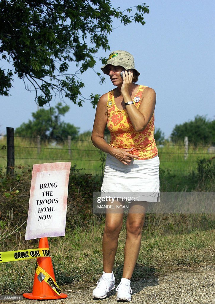 Cindy Sheehan of Gold Star Families for Peace speaks on a mobile phone near her makeshift camp on the side of a road leading to the ranch of US...