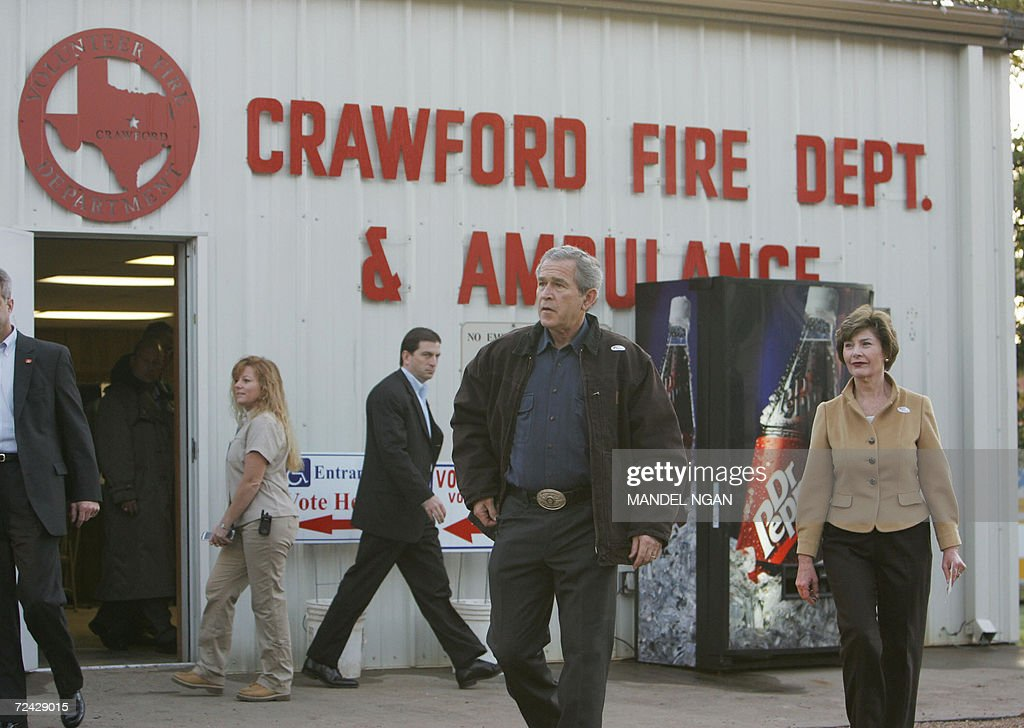 US President George W Bush and First Lady Laura Bush walk toward reporters after walking out of the Crawford Fire station 07 November 2006 after...