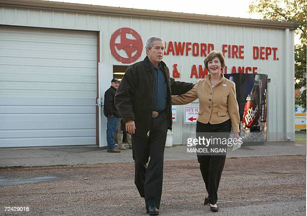 US President George W Bush and First Lady Laura Bush walk toward reporters after stepping out of the Crawford Fire station 07 November 2006 after...