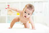 baby boy weared diaper crawling on bed at nursery