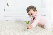 Crawling baby with pacifier in a living room.Copy space, shallow doff