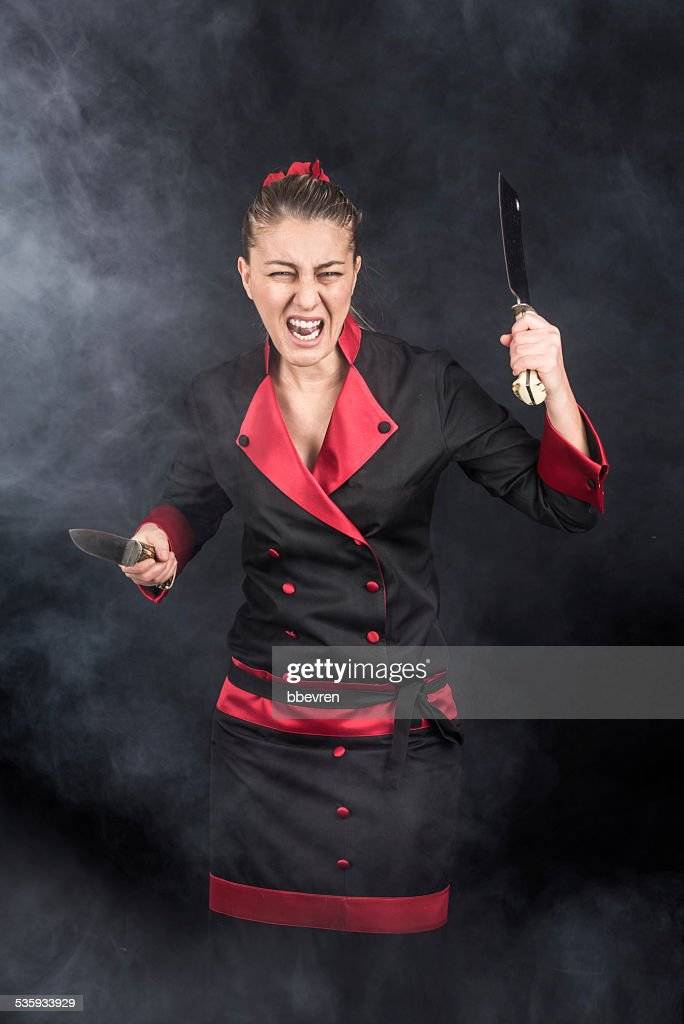 Crazy chef screaming and attacking with her weapons knife : Stock Photo
