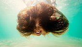 Beautiful young smiling woman swimming underwater in the sea.