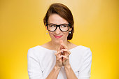 crazy looking sly woman in black glasses isolated on yellow background.