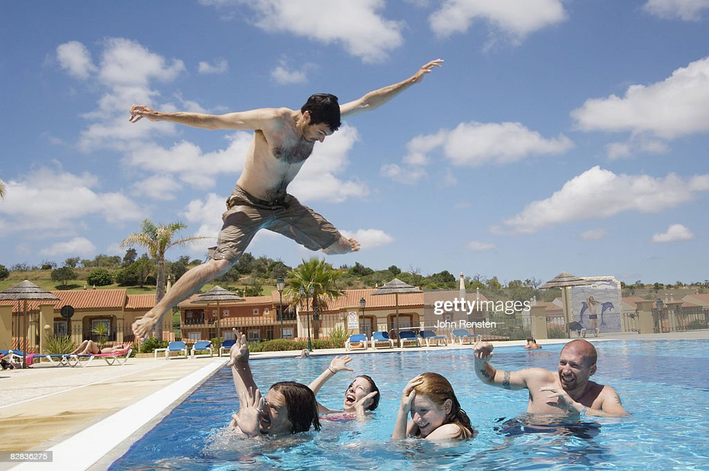 crazy man jumping on friends in swimming pool stock photo