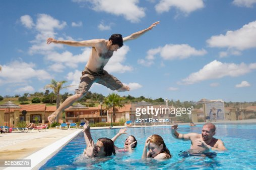 crazy man jumping on friends in swimming pool stock photo getty images
