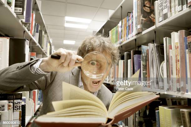 Crazy man looking in book with magnifying glass