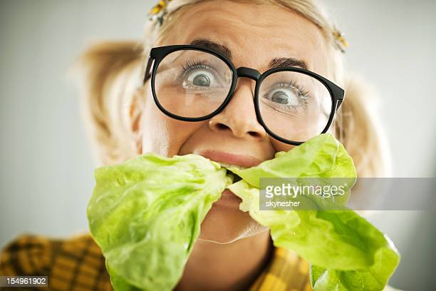 Crazy nerd woman with the cabbage leaf in her mouth.