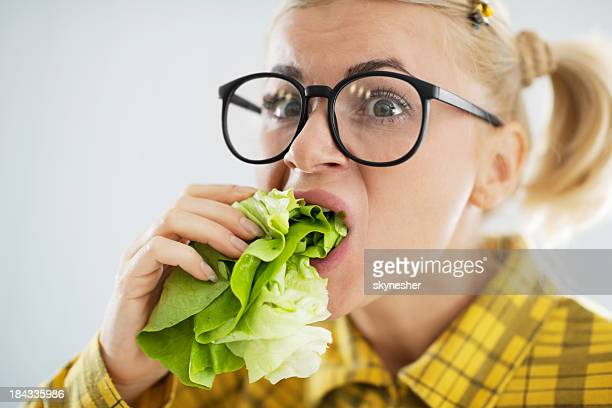 Crazy nerd woman with the cabbage leaf in her mouth