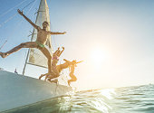 Crazy rich friends jumping off the boat into the ocean - Young happy people having fun diving into the sea at sunset - Travel, tropical, summer, vacation, luxury concept - Soft focus on left man face
