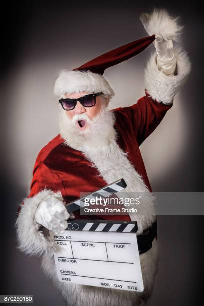Crazy Santa Claus holding a film clapperboard and pulling his hat