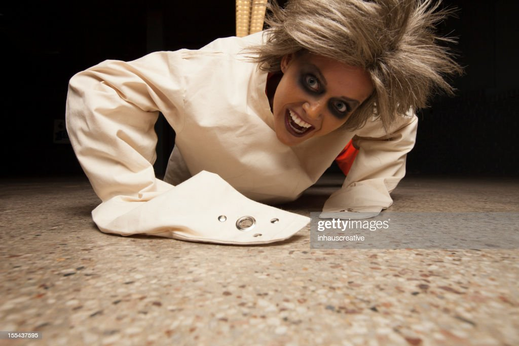 Crazy Woman Wearing A Straight Jacket In An Asylum Crawling Stock ...