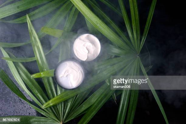 cream aftershave on green leaves and wet background