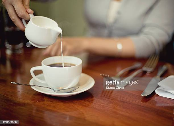 Cream being poured into cup of coffee