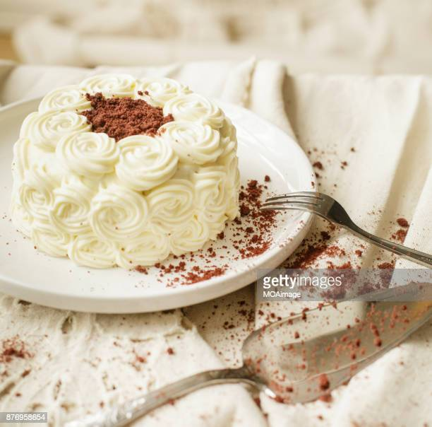 A cream cake on a plate is put on the tablecloth