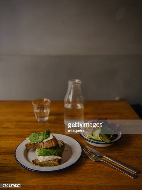 Cream cheese and avocado toast with salad and water