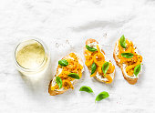 Cream cheese, roasted yellow bell pepper, basil bruschetta and white  wine on light background, top view. Flat lay, copy space