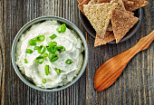 bowl of cream cheese with green onions and herbs, dip sauce on wooden table, top view