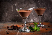 Cream coffee cocktail, chocolate martini with mint on black stone table, copy space