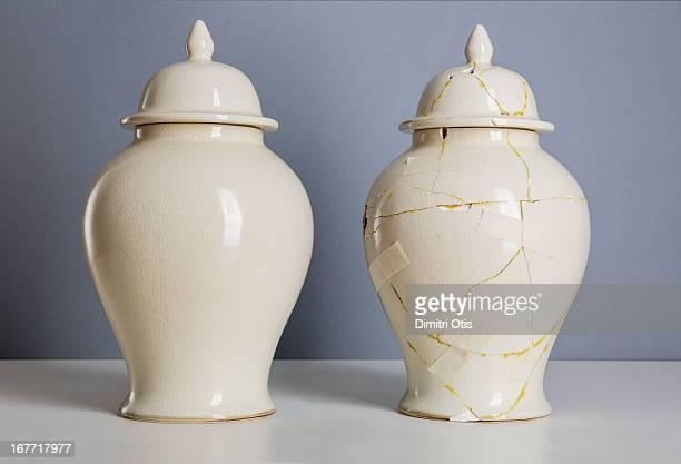 Cream coloured vase next to broken, repaired one